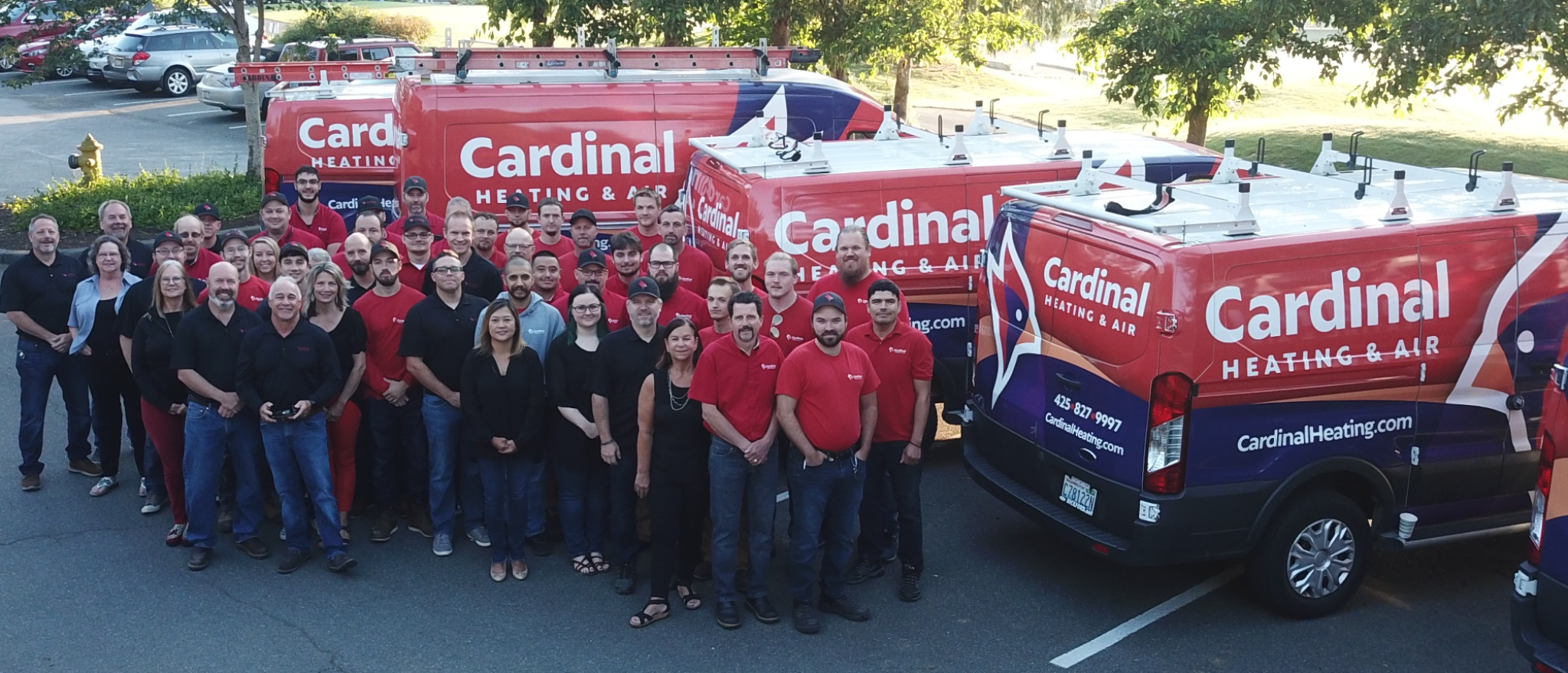 Cardinal Heating and Air employees standing behind their fleet of wrapped commercial vehicles